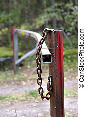 Gate on small road - Gate witt padlock and rusty chain on...
