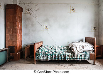 Abandoned bedroom - Bed, TV and stove in adandoned room