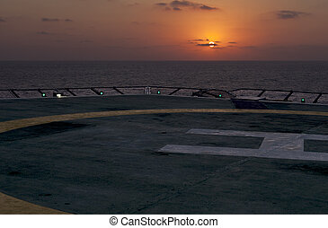 Sunset seen from a helicopter landing pad on board of a...