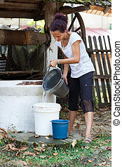 Woman getting water from well - Young woman outdoor getting...