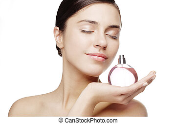 perfume - young female smelling a bottle of perfume