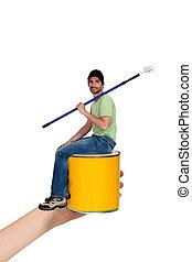 Tiny man sat on paint tin
