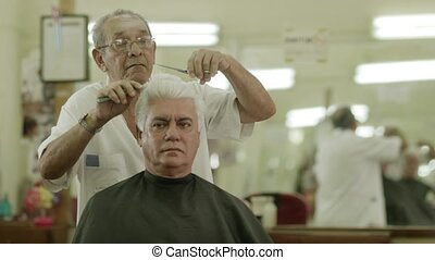 Barber cutting hair to client - Active retired old people,...