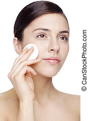 removing makeup - young woman cleaning her face