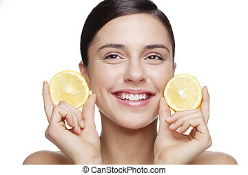 natural skin care - fresh faced young female holding lemon...