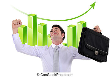 Elated businessman in front of a bar chart
