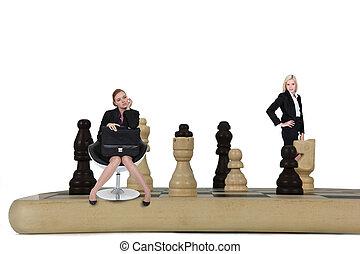 Two women on giant chessboard