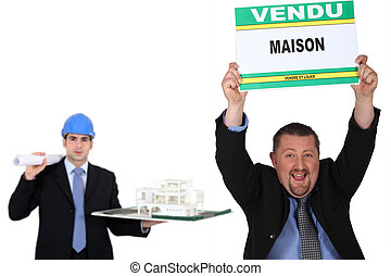 Man holding a french maison vendu sign