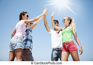 high five - group of young people doing a high five