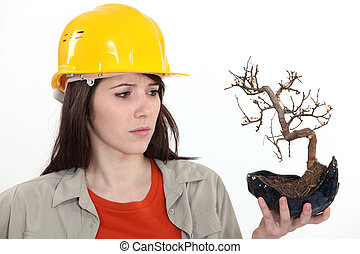 woman holding a dead plant