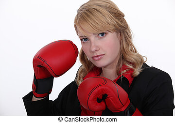 A businesswoman with boxing gloves on