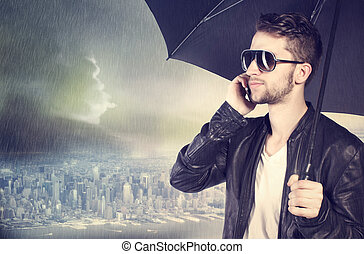 Man talking on his cellphone in the rain - Stylish man...