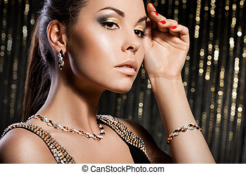 elegant fashionable woman with golden jewelry