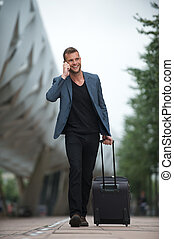 Young Caucasian Man Walking in City with Cell and Suitcase -...