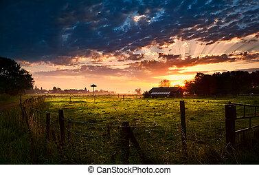 Dutch farmhouse at sunrise - farmhouse with fence at summer...