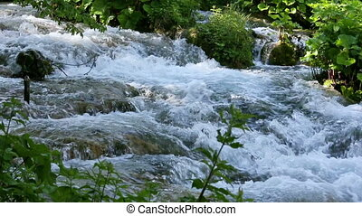 Summer mountain river with rapid current in Plitvice Lakes...