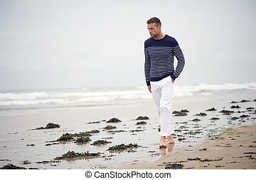 Man Walking Alone on the Beach - A young man walking on the...