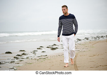 Man Walking on the Beach Looking out to Sea - A young man...