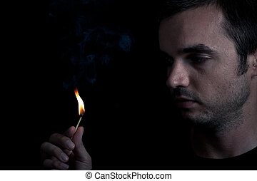 Man and fire - Dramatic portrait of man lighting safety...