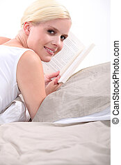 Young blond woman reading a book on her bed