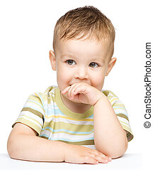 Portrait of a cute little boy looking at something while...