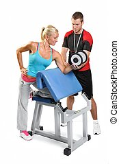 Beautiful woman exercising with personal fitness trainer on a white background