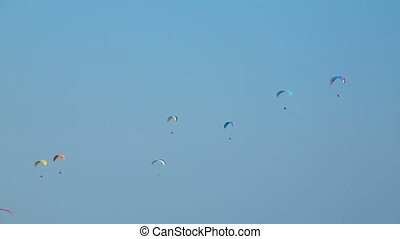 Gliding on a sunny day - Numerous paragliders flying in the...