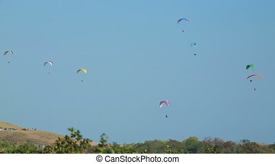 Gliding above the field - Lots of paraplanes flying above a...