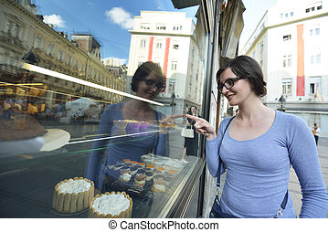 woman in front of sweet store window