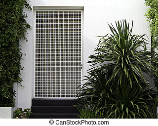 White wall entrance with garden