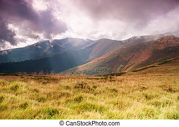 Landscape with sunrays - Autumnal hills high up in...