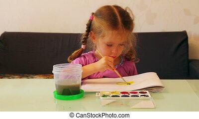 little girl draws paints