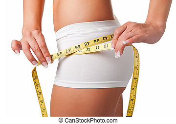 Diet Time - Woman measuring her waist with a yellow...