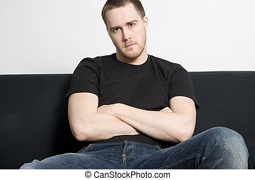young man sitting on a black sofa