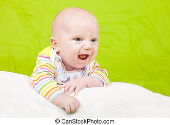 The happy childhood - The cheerful kid lies on a pillow. The...