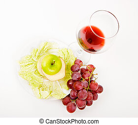 green apple in a glass of wine and grapes