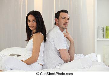 Couple sitting back to back