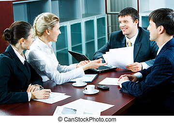 Business briefing - Photo of four business people discussing...