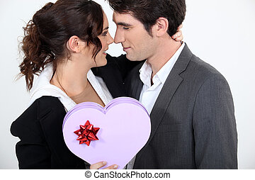 Couple holding heart-shaped box of chocolates