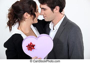 Couple holding heart-shaped box of chocolates