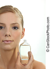 Blond woman holding perfume bottle