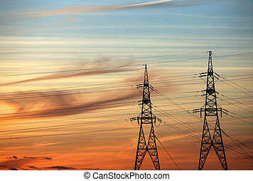 High voltage tower on a background of the red sky