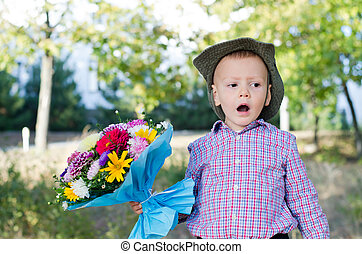 Self-conscious little boy singing with a large bouquet of...