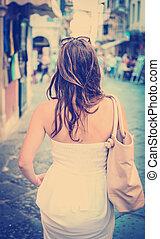 Woman in white dress walking - Rear view