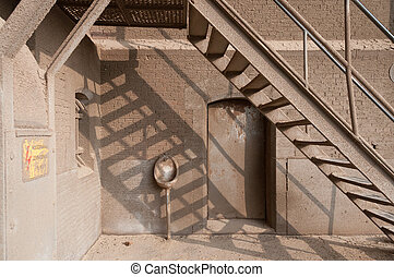 Urinal against wal under stair in old warehouse, port of...
