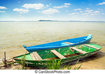bank of lake - two boats and cane on the bank of lake