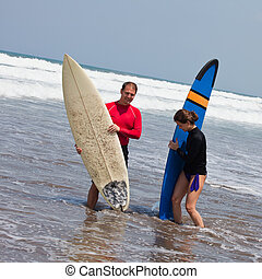 Two surfers on an ocean coast - young man and the girl with...