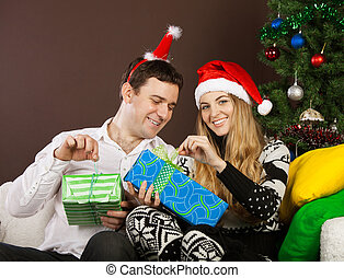Happy couple near the Christmas tree - Happy couple in...