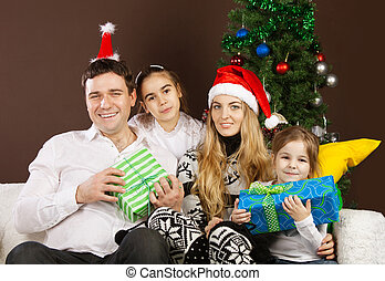 Happy family near the Christmas tree - Happy family with...