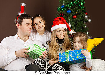 Happy family near the Christmas tree - Happy family opening...